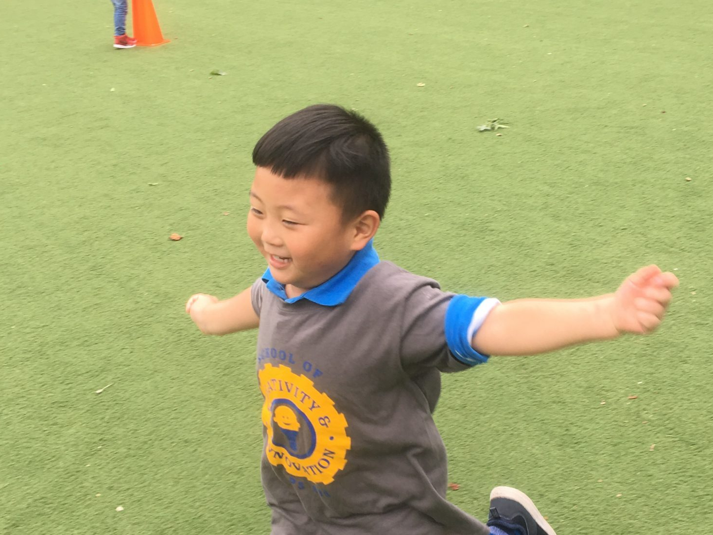 student crosses the finish line at field day