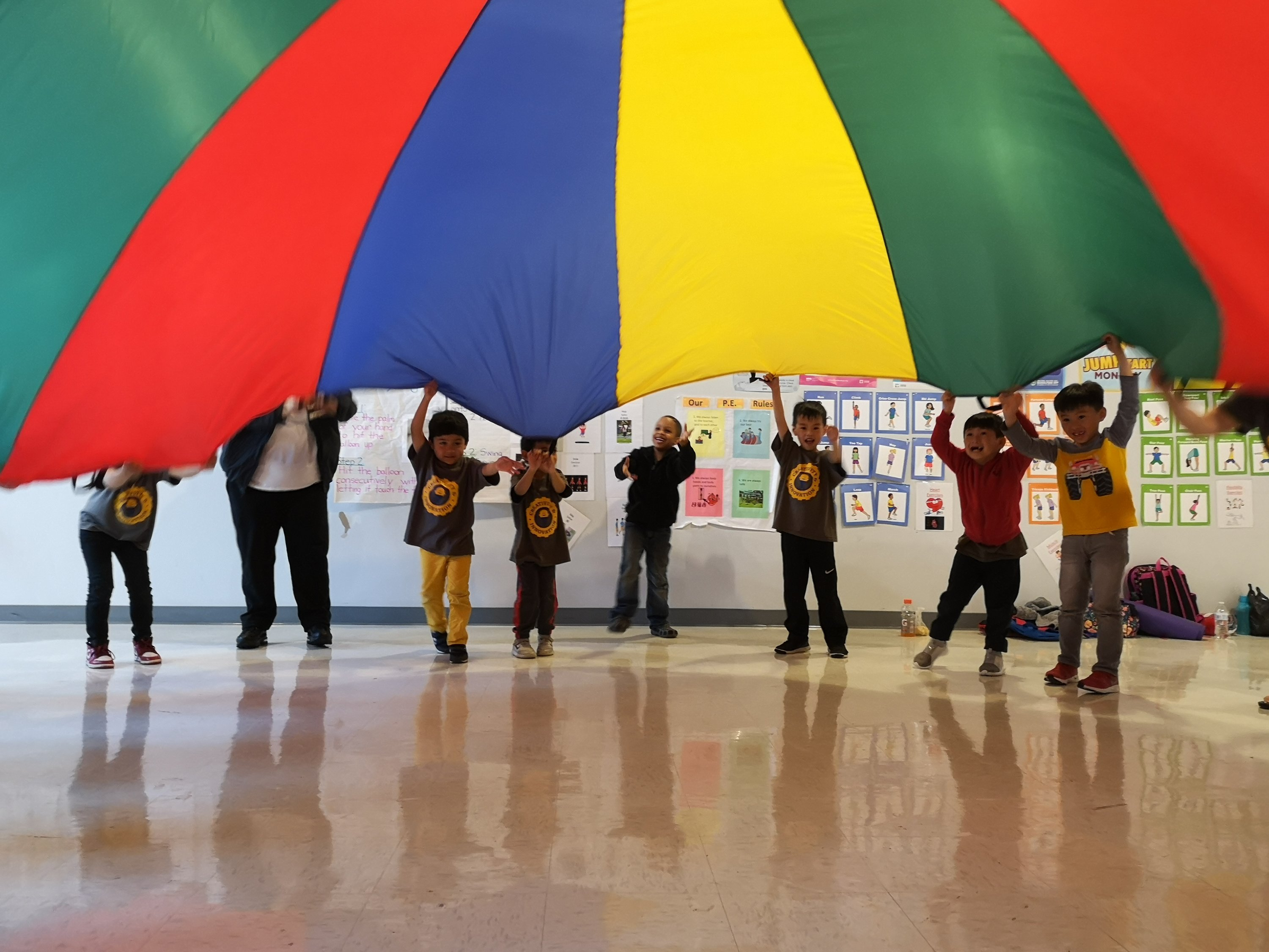 students holding up parachute