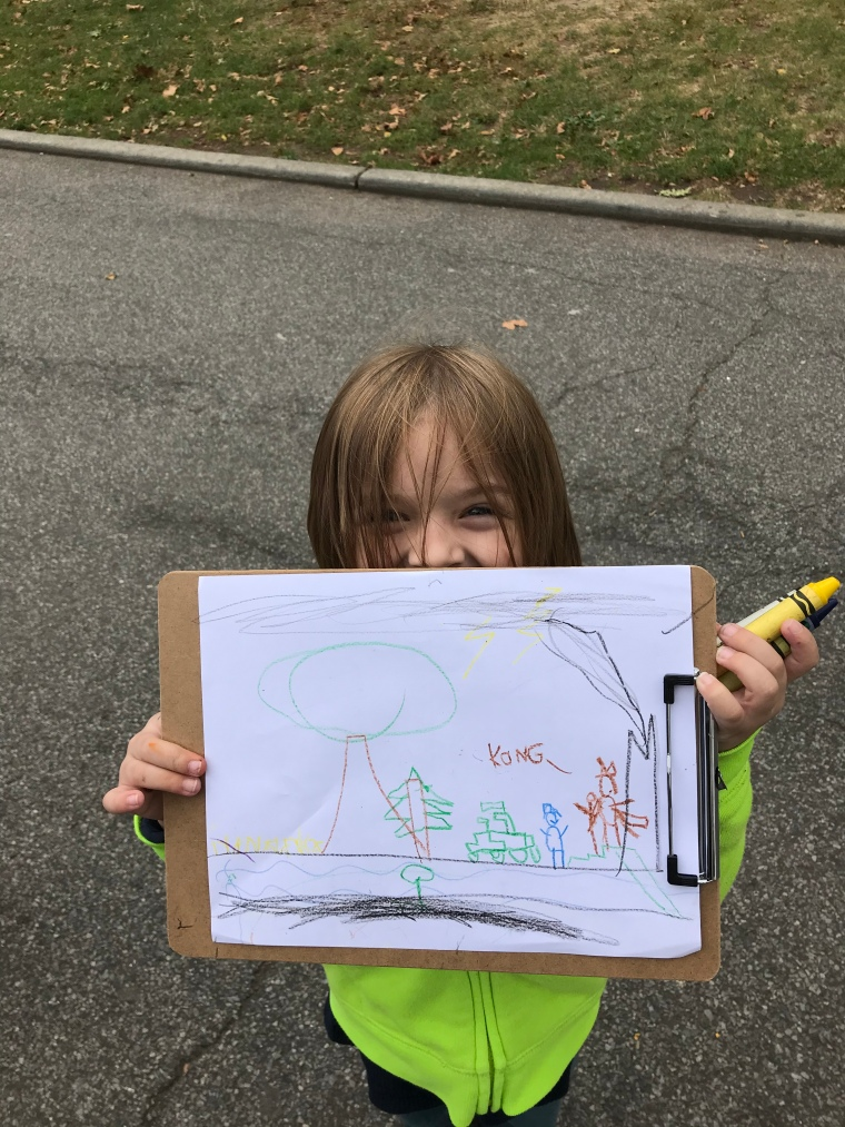 Student holding artwork in the park
