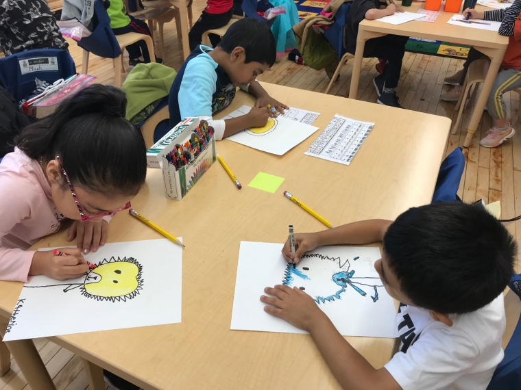 3 kids drawing pictures in a classroom