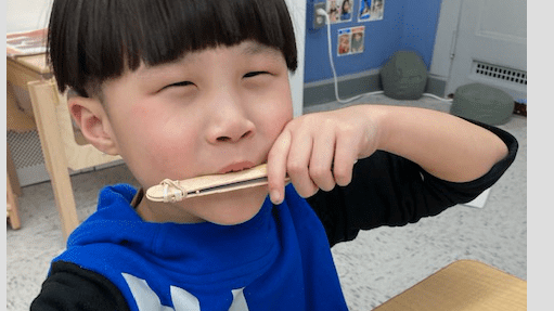 student on harmonica